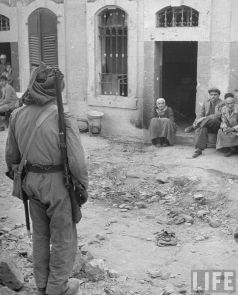 Arab soldier standing guard in the Jewish qarter in Jerusalem. June 1948. John Phillips.